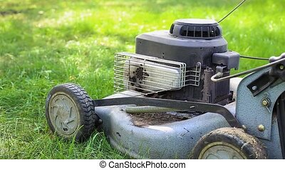 lawn mower stands on the grass - a lawn mower is standing on...