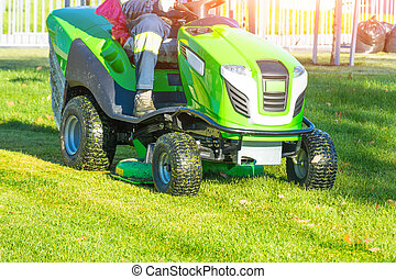 Lawn mower with driver mowing the grass on a green meadow.