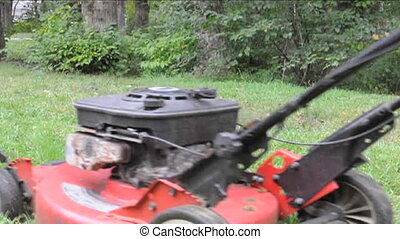 lawn mowing power machine - man mowing grass lawn detail...