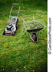 lawnmower and wheelbarrow with grass on mown green lawn