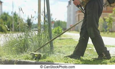 Lawnmower man mows grass