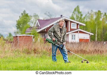 Lawnmower man with cottage on background grren grass