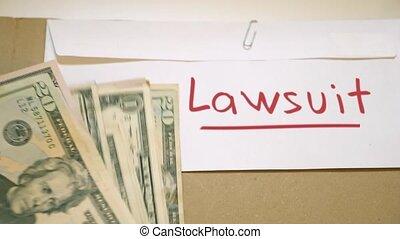 Lawsuit costs concept - USD bills on lawsuit envelope