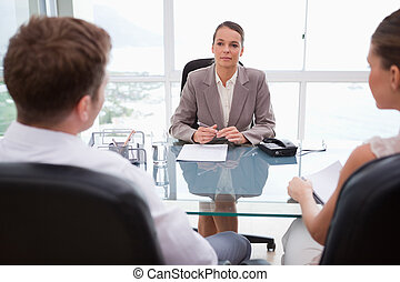 Lawyer advising her clients in her office
