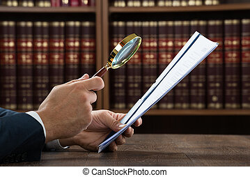 Lawyer Examining Documents With Magnifying Glass - Cropped...