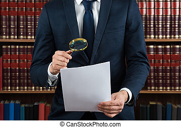Lawyer Examining Legal Documents With Magnifying Glass -...
