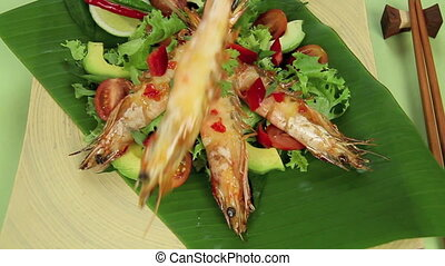 Lay Down Asian Prawn - Putting skewered Asian shrimps onto a...