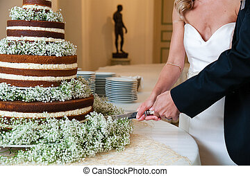 layered chocolate wedding cake with white and green flowers being cut by a bride and groom with a knife