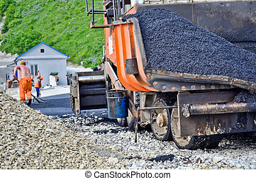 laying asphalt. asphalt paver machine and worker.