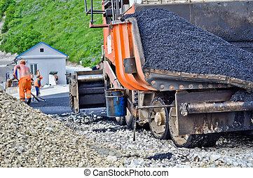laying asphalt. asphalt paver machine and worker.