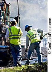 Laying Asphalt - Two men working alongside an asphalt paving...