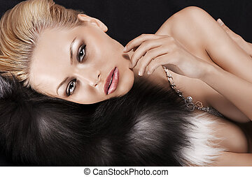 laying blonde pretty girl on black fur