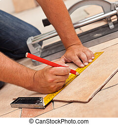 Laying ceramic floor tiles - man hands marking tile to be cut, closeup