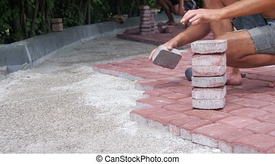 Laying Colored Tiles in a City Park. Laying Paving Slabs by...