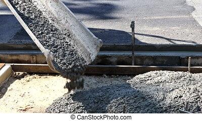 Laying down new sidewalk in wet concrete on freshly poured sidewalks