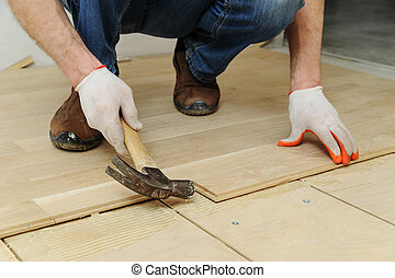 Laying hardwood parquet.