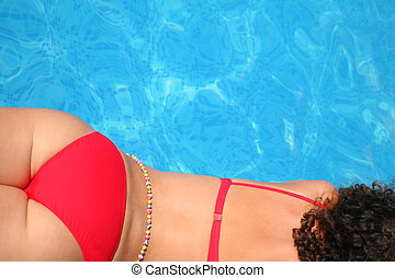 Laying in bikini girl from back near pool