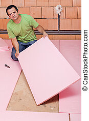 Laying insulation layer in a new house - Worker laying...