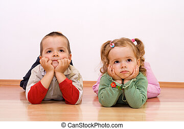 Laying on the floor - Two kids bored, looking at something -...