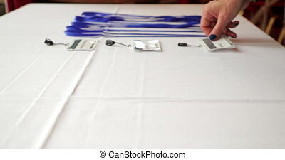 Laying Out Lanyards - Close-up of a businesswoman laying out...