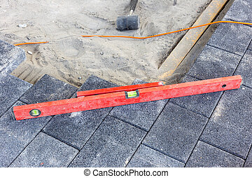 laying paving stones on the terrace with tools