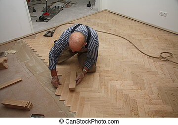 Man laying a wooden parquetry flooring in fishbone pattern