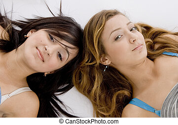 laying young girls looking to camera on an isolated white ...