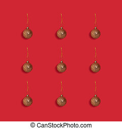 Layout of golden glittering Christmas balls on a red background.