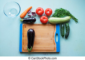 Layout of whole and sliced eggplants, cutting board and other fresh vegetables.