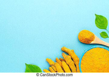Layout with turmeric powder in blue bowl with wooden spoon and dried roots at blue background.