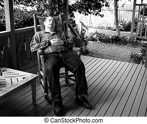Man napping in a rocking chair on front porch