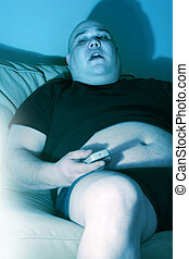 Lazy couch potato - Lazy overweight male sitting on a couch ...