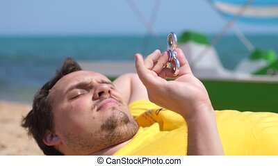 Lazy fat bearded man lies on the beach twists the...