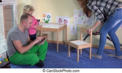 Lazy father with little daughter girl using tablet and mother hoover floor