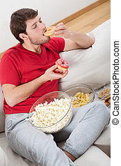 Lazy guy on a couch with food