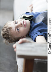 little child lying on sofa looking into camera