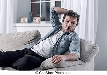 Lazy man resting on the sofa instead of looking for a job