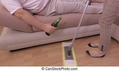 Lazy man with beer on sofa near woman who cleaning floor