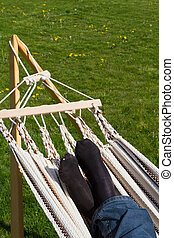 Lazy on the hammock - Lazy feet rest on the hammock in the...