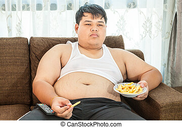 Lazy overweight male sitting with fast food