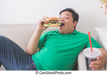 lazy overweight man eating hamburger while laying on a couch