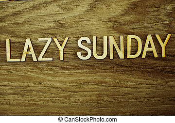 Lazy Sunday text message on wooden background