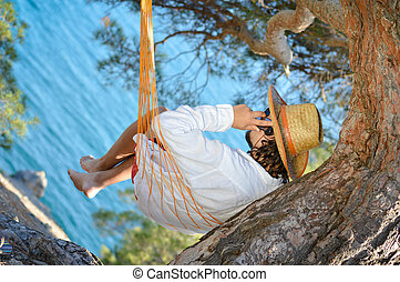 Lazy time. Man in hat in a hammock on pine tree in Crimea a summer day