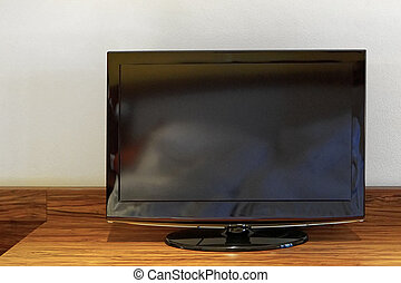 Lcd TV - Black lcd TV set at wooden shelf