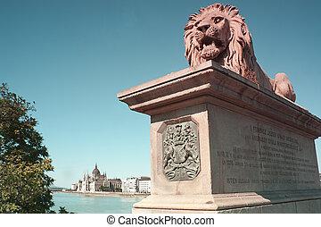 león, estatua, en, el, cadena el puente, proteger, el, húngaro, edificio del parlamento, en, el, azul, río de danubio, en, budapest, hungría