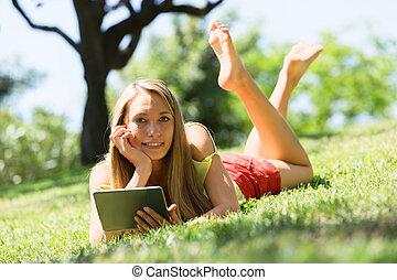 leżący, ereader, dziewczyna, cieszący się, trawa, szczęśliwy...