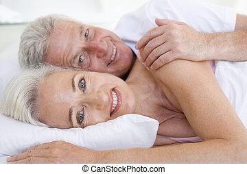 leżący, para, łóżko, razem, uśmiechanie się