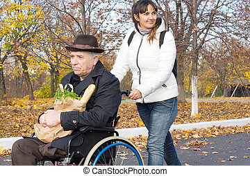 le, carer, pressande, en, gammal man, in, a, rullstol