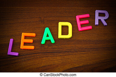 Leader in colorful toy letters on wood background