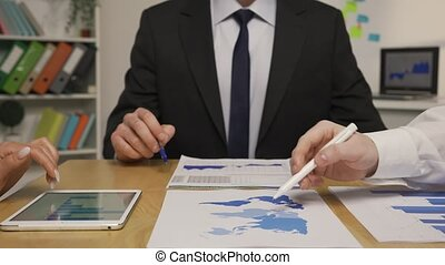 Leader man and partners analyze papers with charts and graphs. Female hands use tablet to check information. Discussion of project in corporate meeting. Close up. Slow motion ready, 4K at 59.94fps.